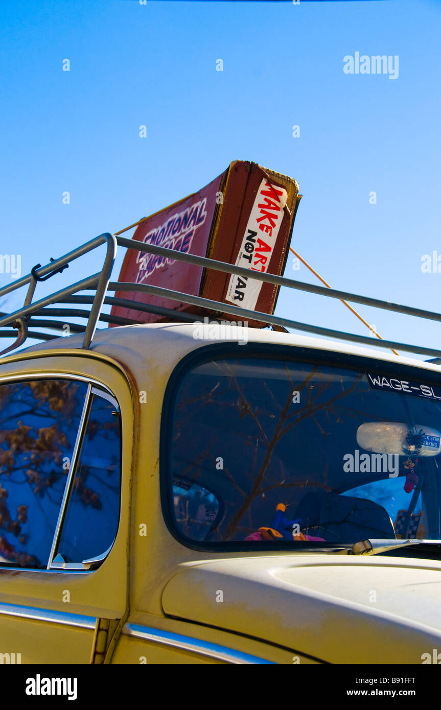 Old suitcase atop car rack on VW bug - Stock Image