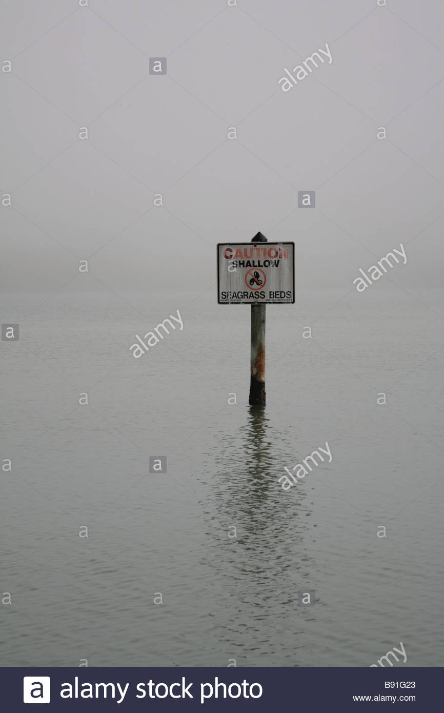 A sign warns of shallow seagrass beds on the Cocohatchee River in Naples Florida - Stock Image
