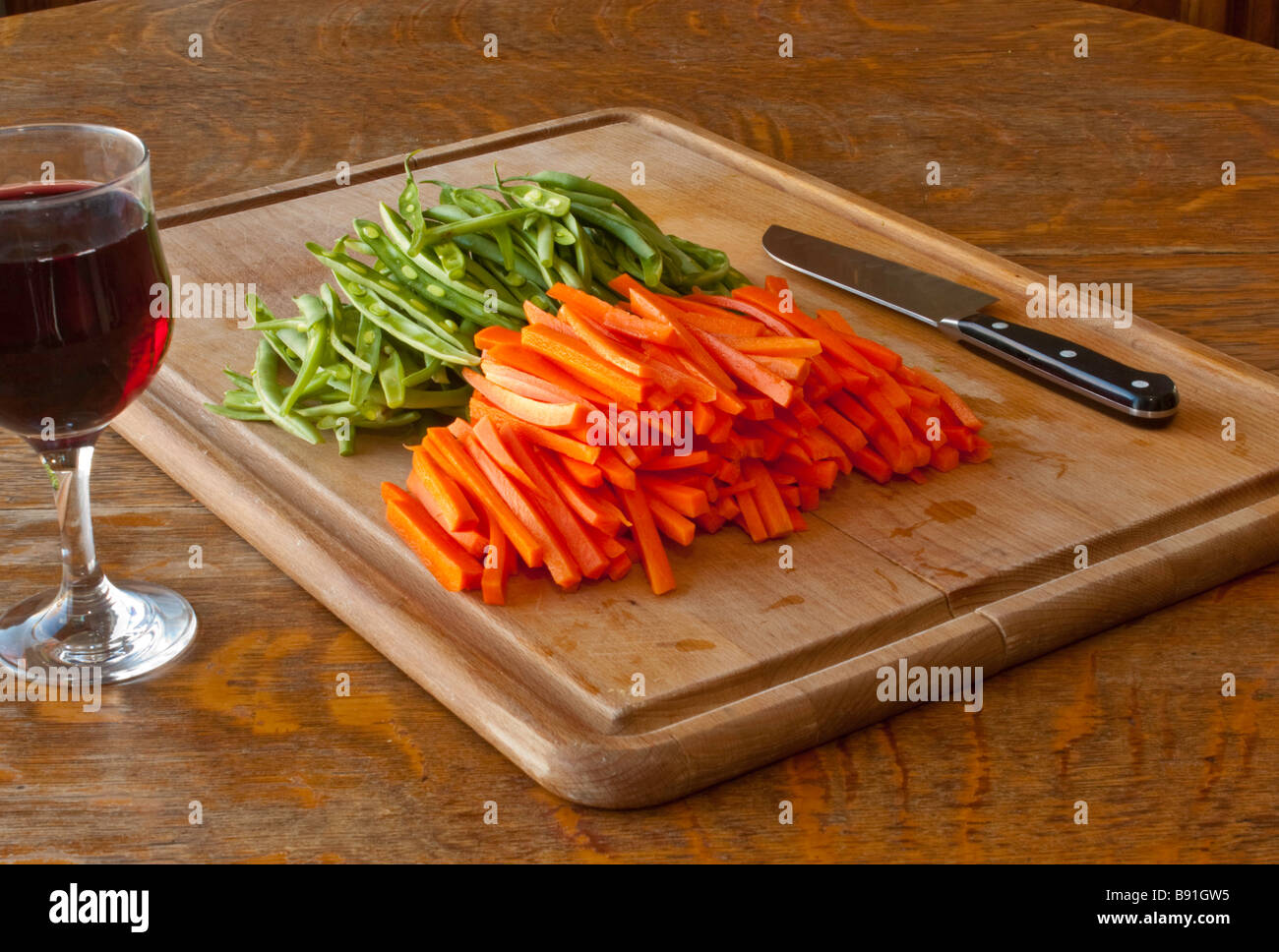 A cutting board with julienned carrots and green beans with a knife and a glass of wine for the chef - Stock Image