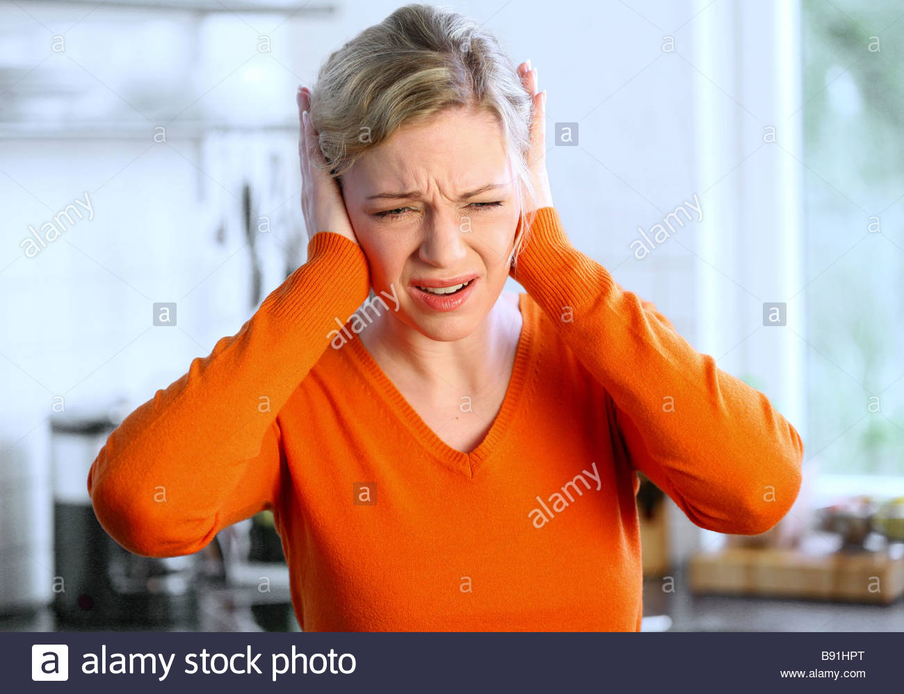 young blonde woman covering her ears with hands - Stock Image