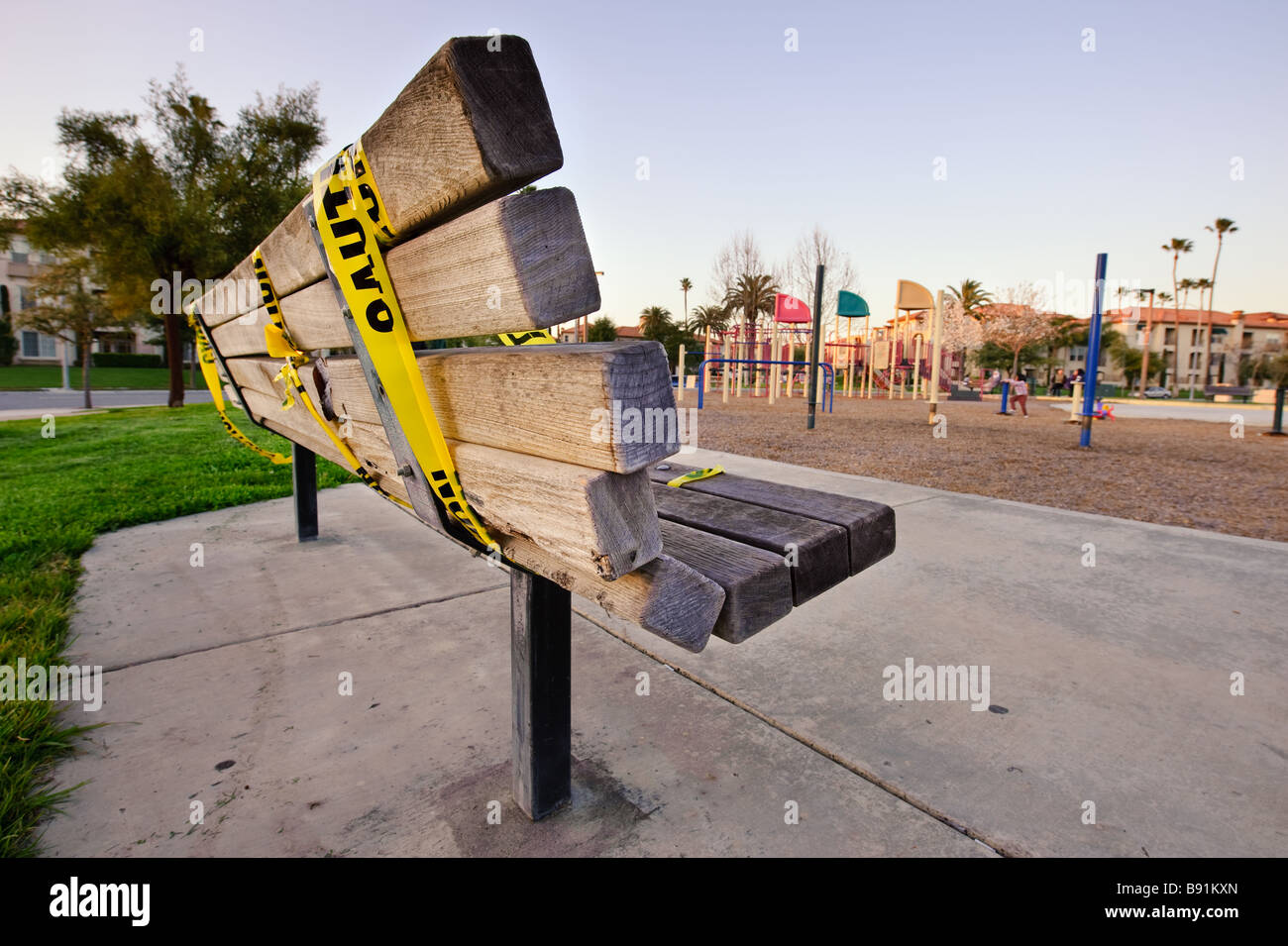 Empty park bench with cation tape wrapped around it with a childrens' playground in the background. - Stock Image
