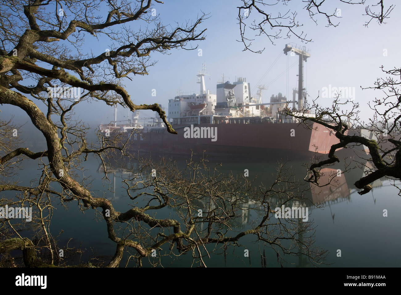 Ship laid up on the river Fal in Cornwall during the global economic downturn in the mist - Stock Image