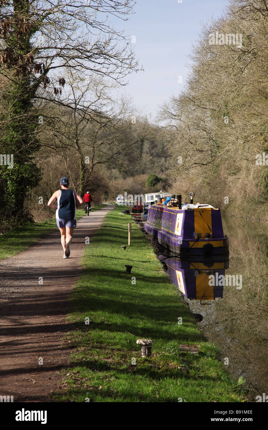 Running & Cycling along the Kennet & Avon canal towpath at Avoncliff near Bradford on Avon, Wiltshire, UK - Stock Image