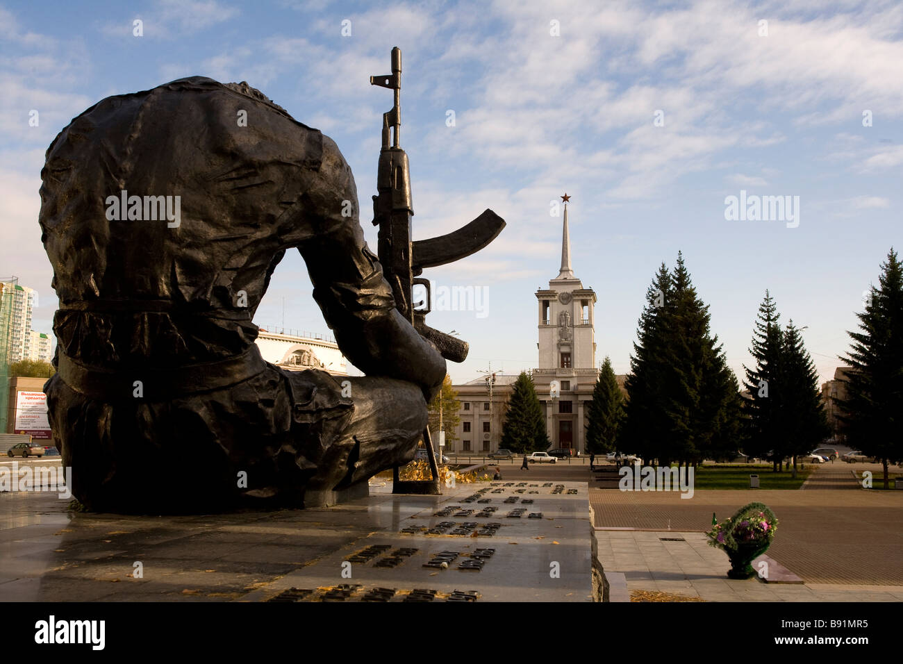 Ekaterinburg, Yakaterinburg Russia chechnya War memorial with the old KGB Headquarters in teh background - Stock Image