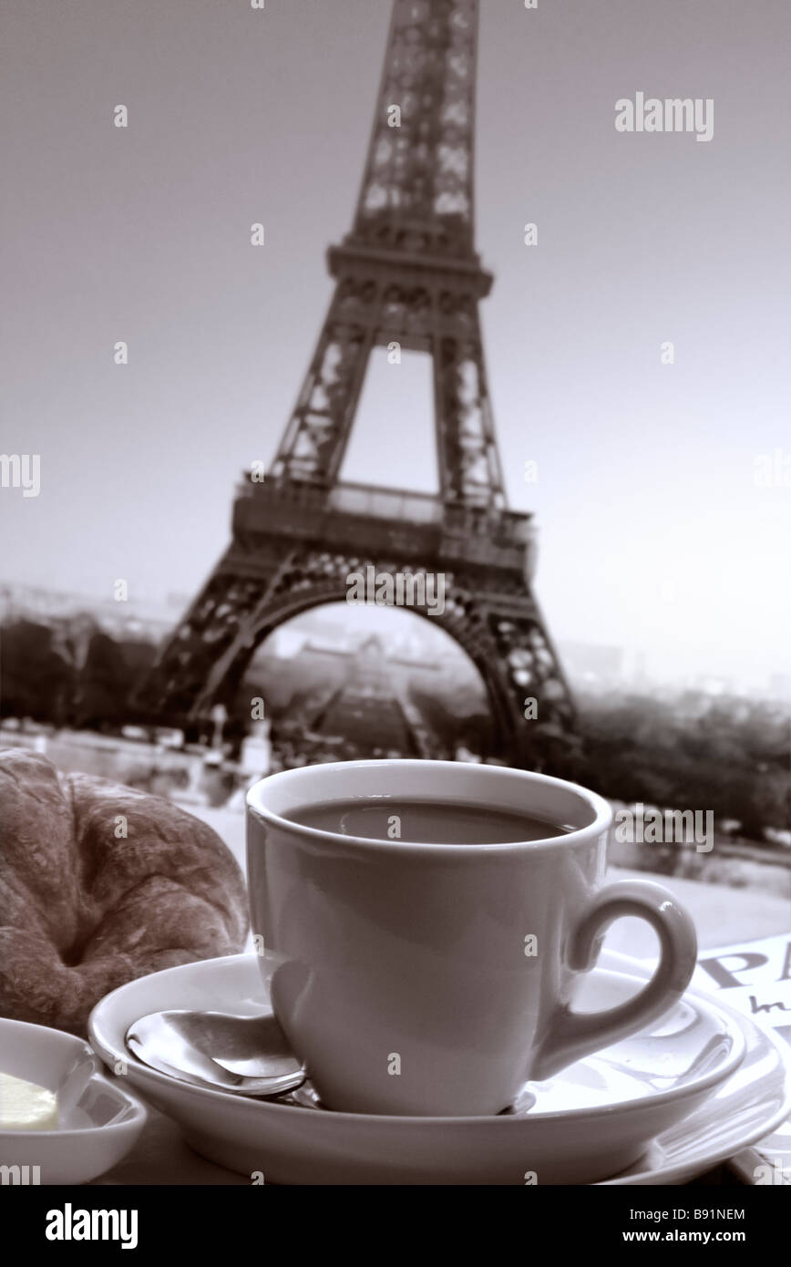 Parisian French breakfast of coffee and croissant on table with guide book and Eiffel Tower behind Paris France - Stock Image