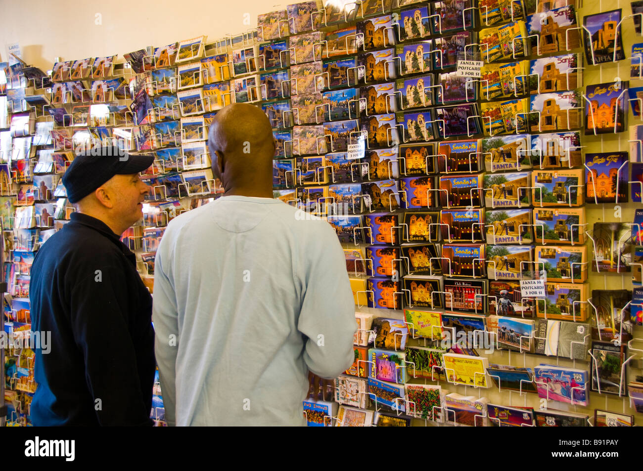 Two male tourists looking at wall of postcards - Stock Image