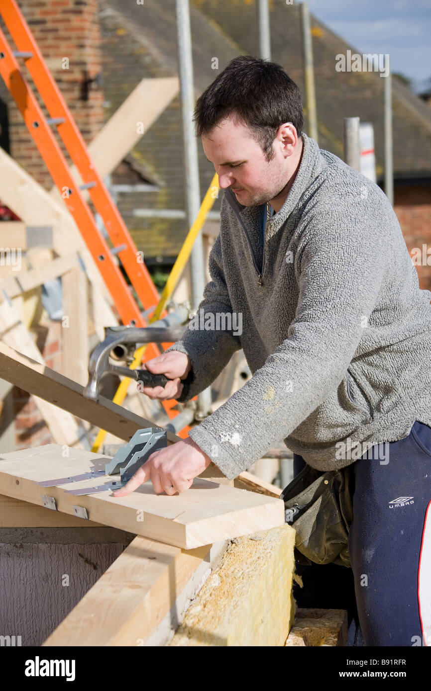 Nailing a mono- truss hanger to a joist infill. - Stock Image