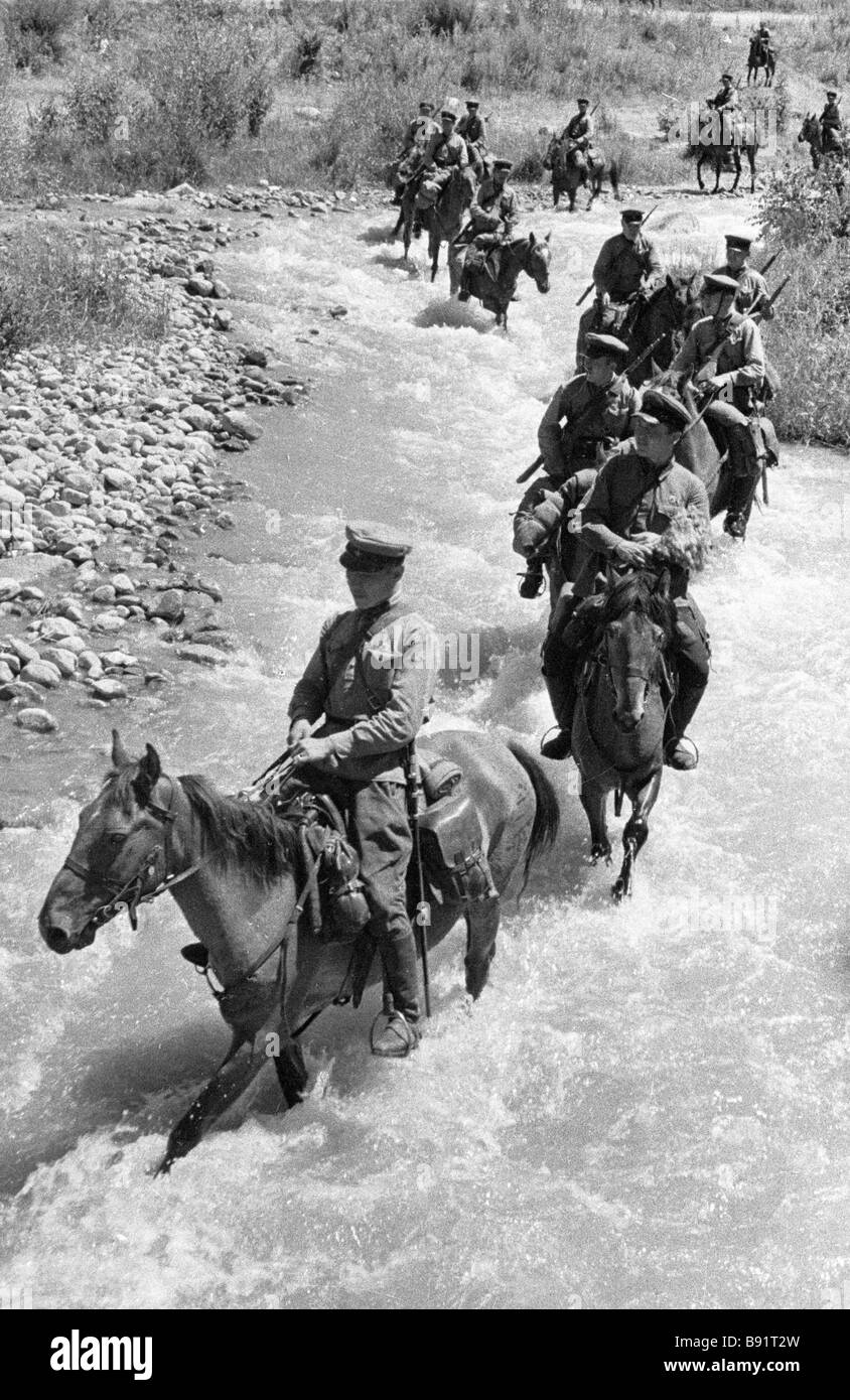 A cavalry unit moves along the bed of a mountain river Turkestan Military District 1932 - Stock Image