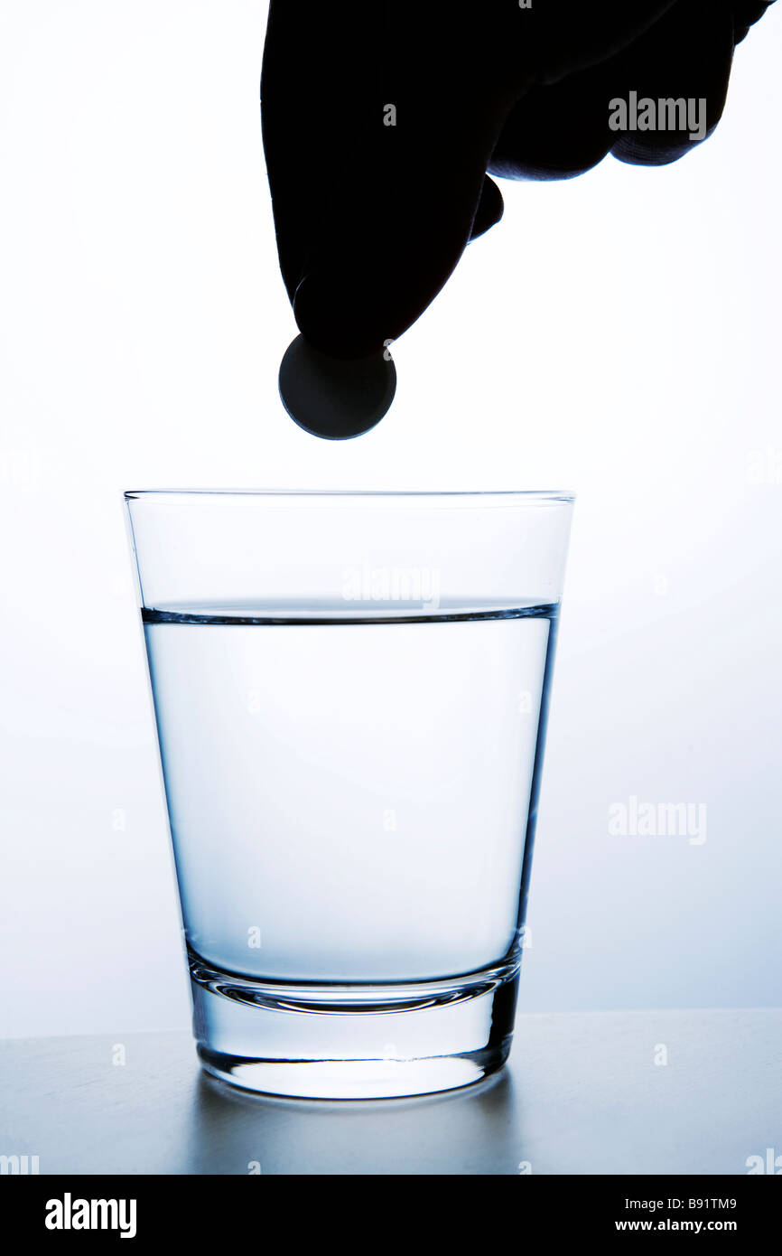 An effervescent tablet and a glass of water close-up. - Stock Image