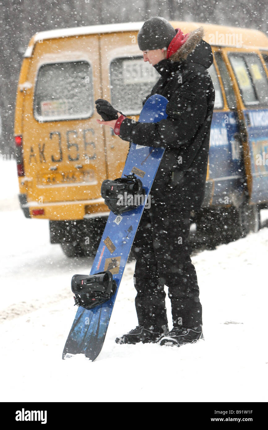 Snowboard skier at a fixed route taxi stop - Stock Image