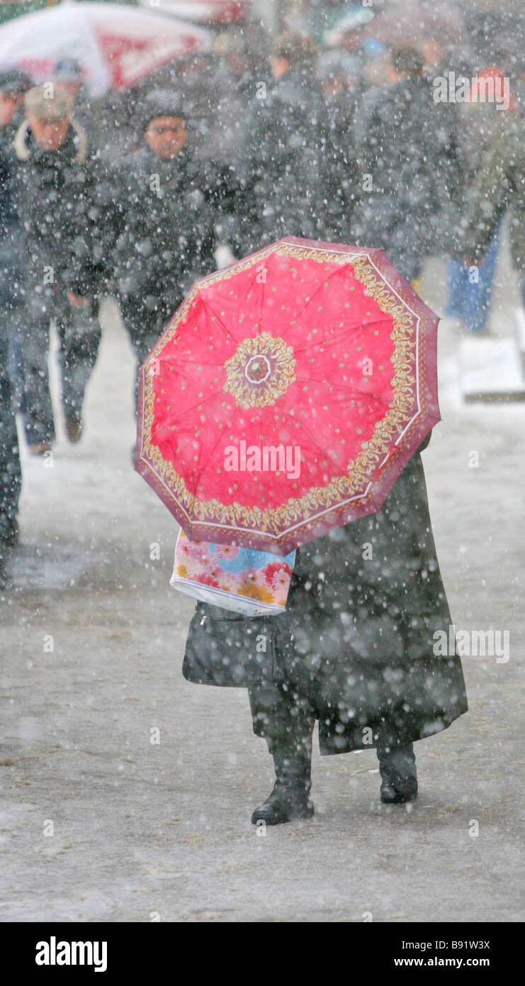 A lady caught in a blizzard in a Moscow street - Stock Image