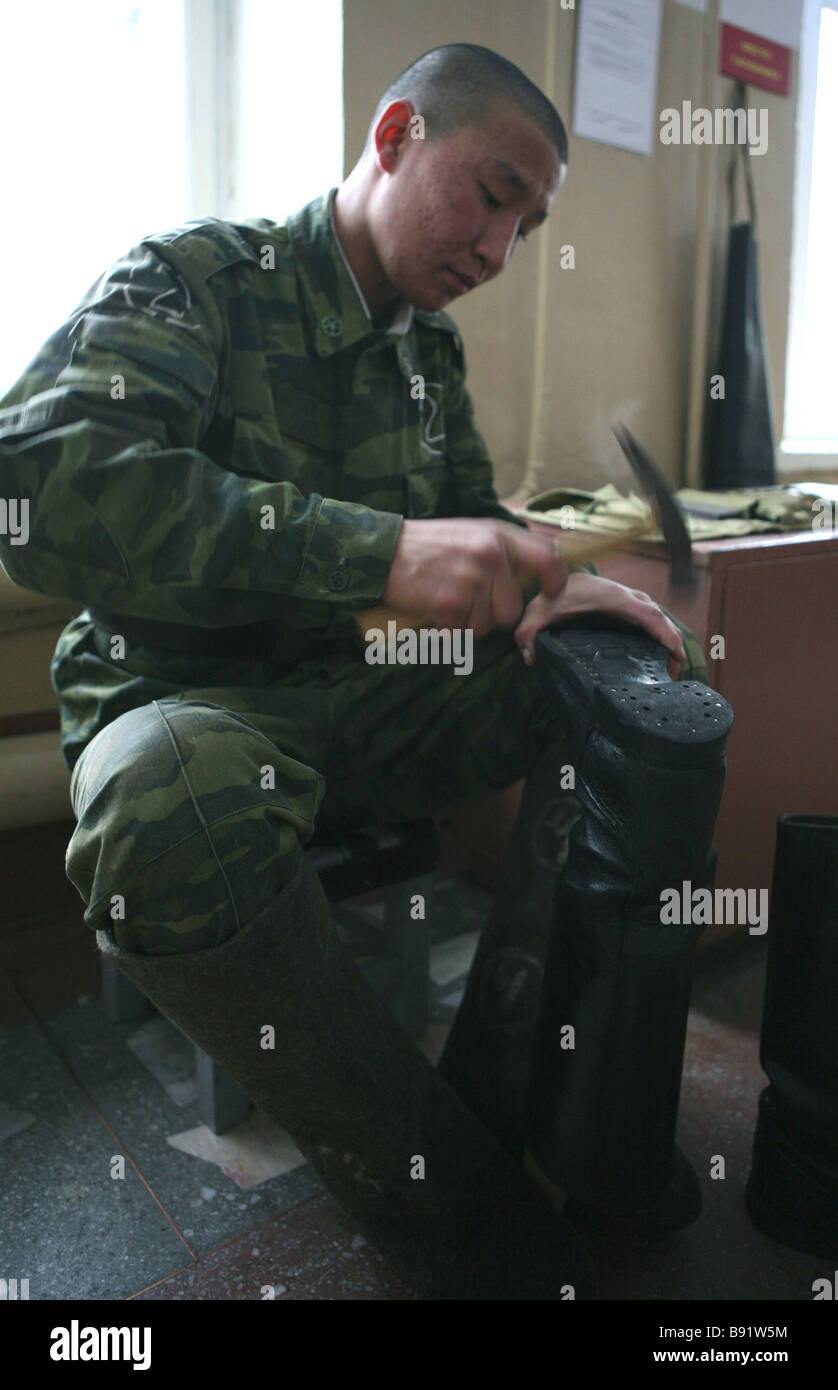 A serviceman repairing shoes Daily life in the Independent Military Correctional Battalion of the Siberian Military - Stock Image