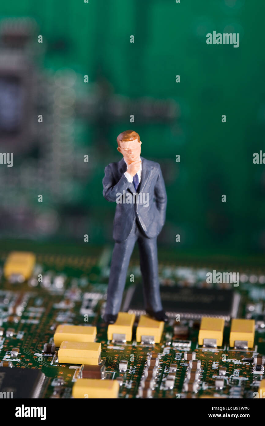 Figure in the shape of a business man standing in a printed circuit card. - Stock Image