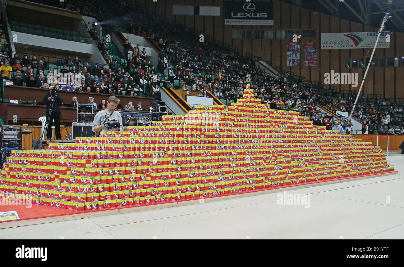 Specially trained Krasnoyarsk students broke a world record and built the largest two meter high canned beef pyramid Stock Photo