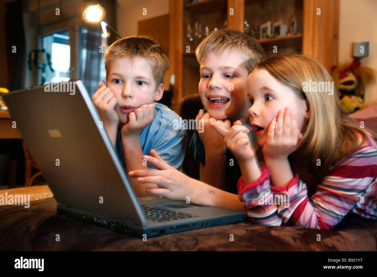 2 brothers and her sister, 7, 11 and 13 years old, playing a learning game, a quiz, at home. Stock Photo