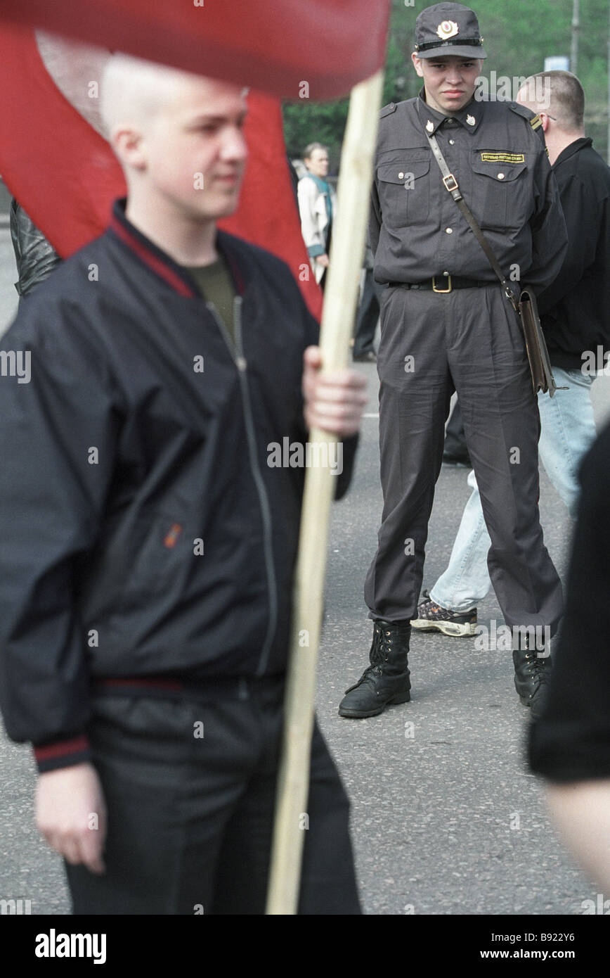 A policeman watching a May Day demonstrator - Stock Image
