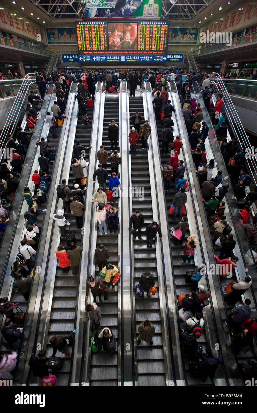 Escalators carrying passengers to trains inside Beijing West Railway Station China - Stock Image
