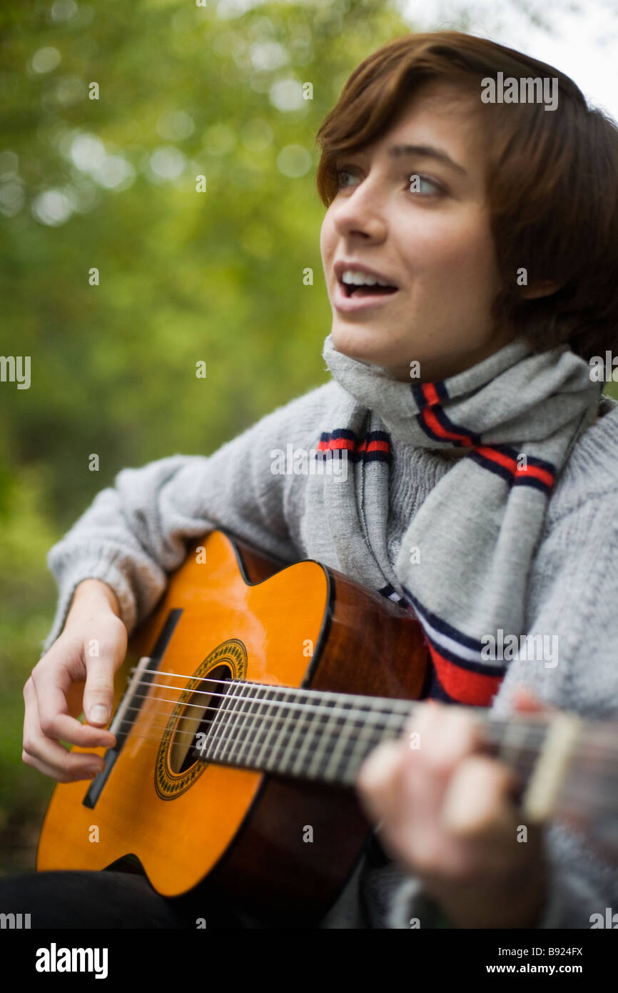 A young woman playing the guitar in the garden Sweden. - Stock Image