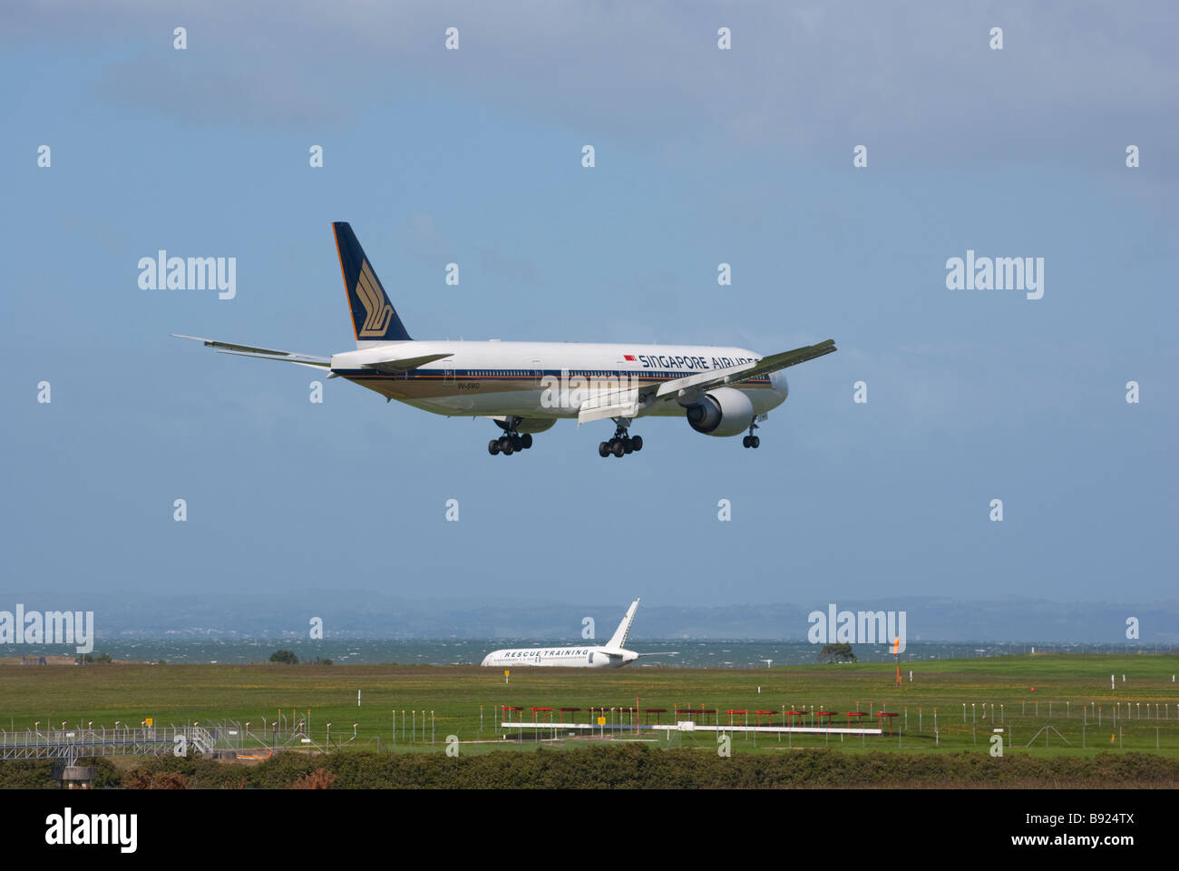 Boeing 777-312ER of Singapore Airlines on final approach for landing at Auckland International Airport. - Stock Image