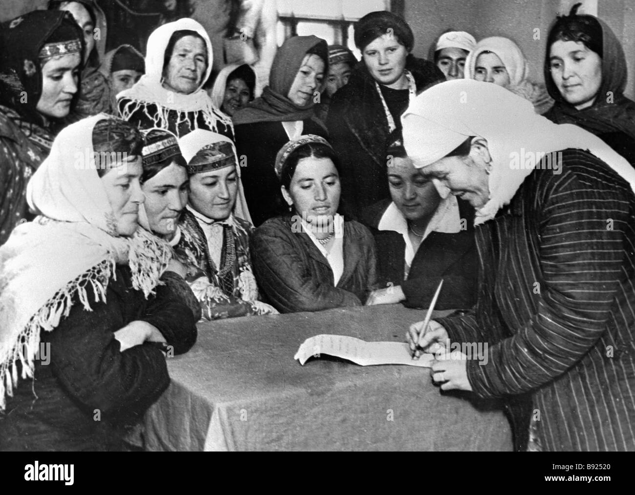 S Sayanova a worker of the Stalinabad sewing factory and deputy of the municipal council signing an appeal to the - Stock Image