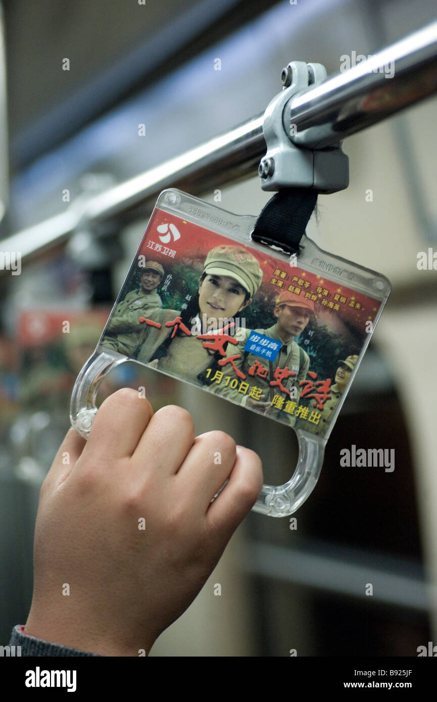 Detail of advertising on hand strap in carriage on new subway train on Line 10 in Beijing - Stock Image