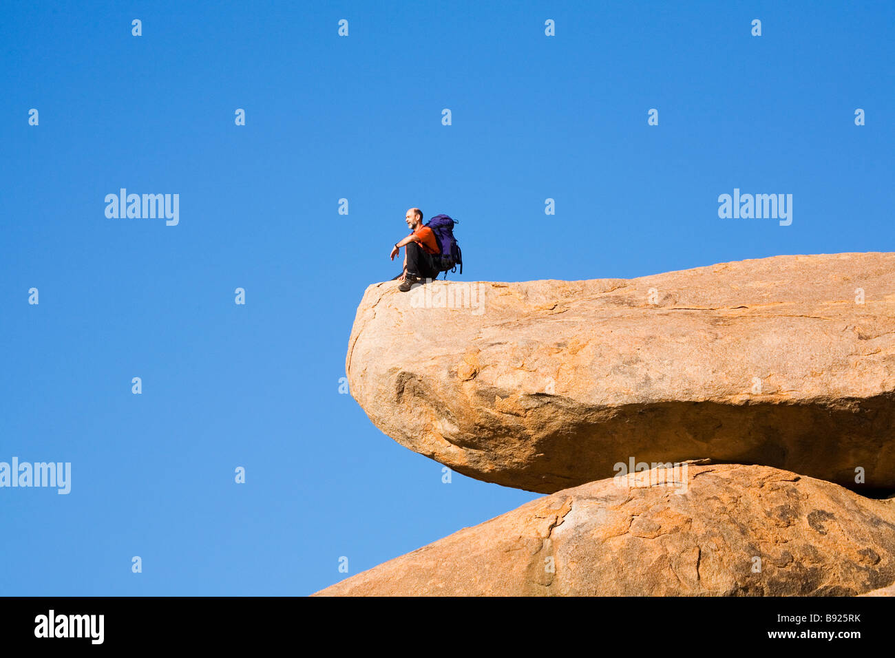 Man sitting on rock staring out at the view bellow, low angle view. Richtersveld National Park, Northern Cape, South - Stock Image