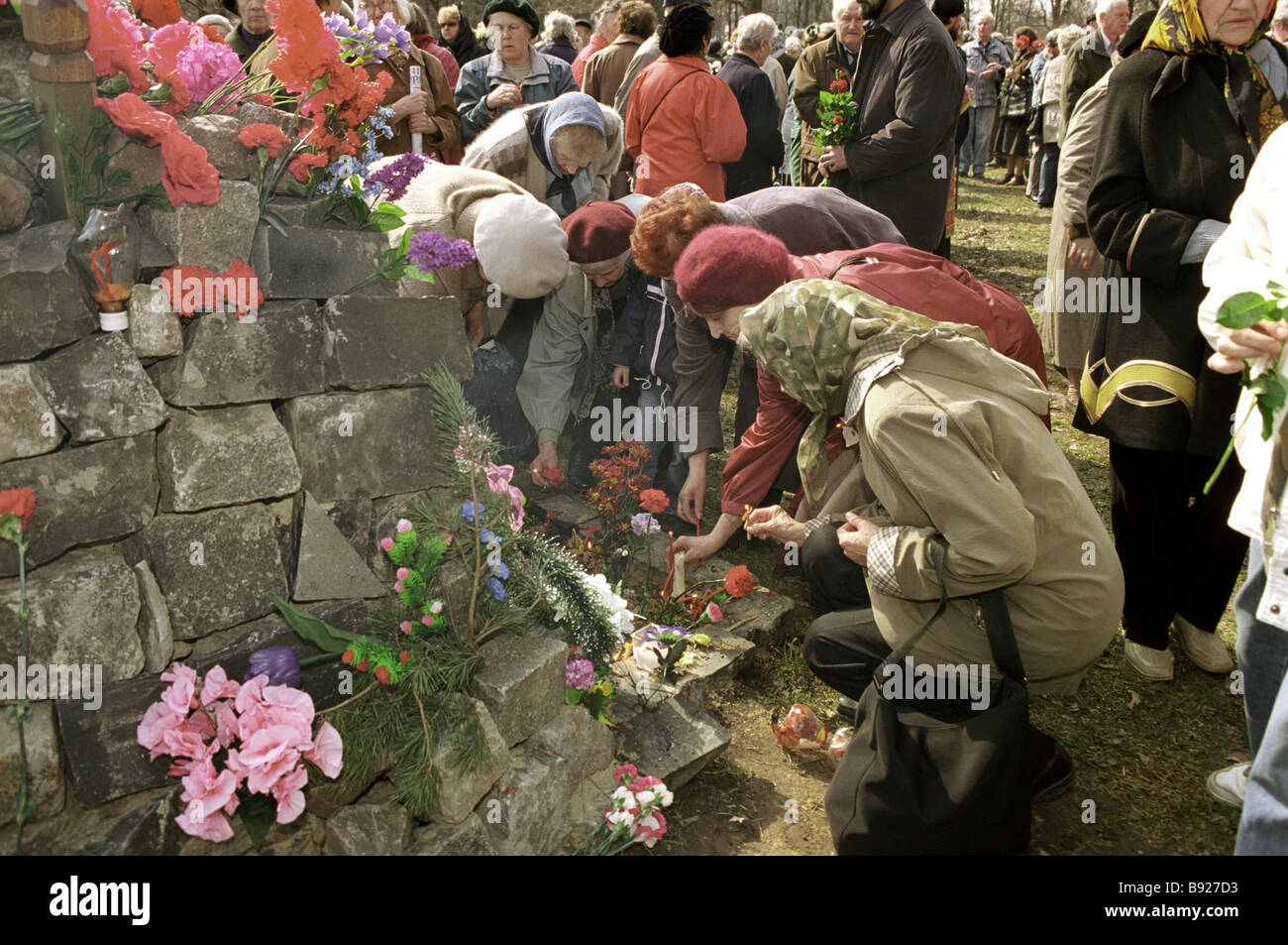 Laying flowers to the common grave of Stalinist victims who found their death by the firing squad at the NKVD shooting - Stock Image
