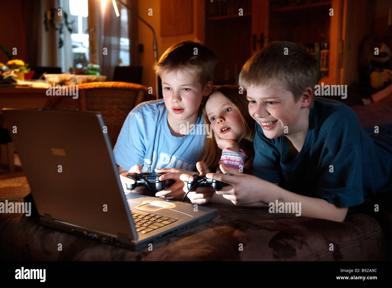 2 brothers and her sister, 7, 11 and 13 years old, playing a computer game, car race, at home. Stock Photo