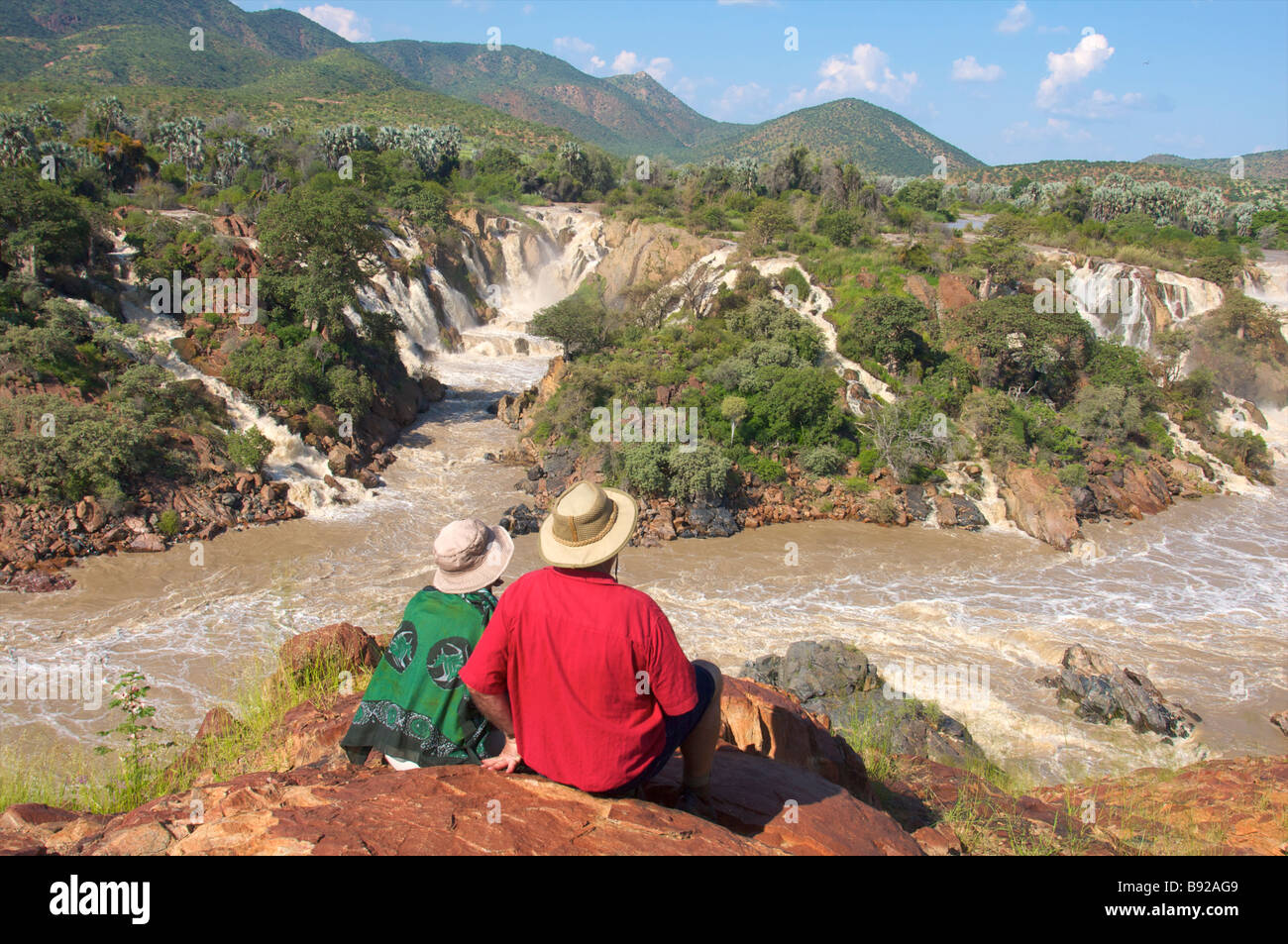 Couple admiring falls Epupa Falls Kunene River Kaokoland Namibia - Stock Image