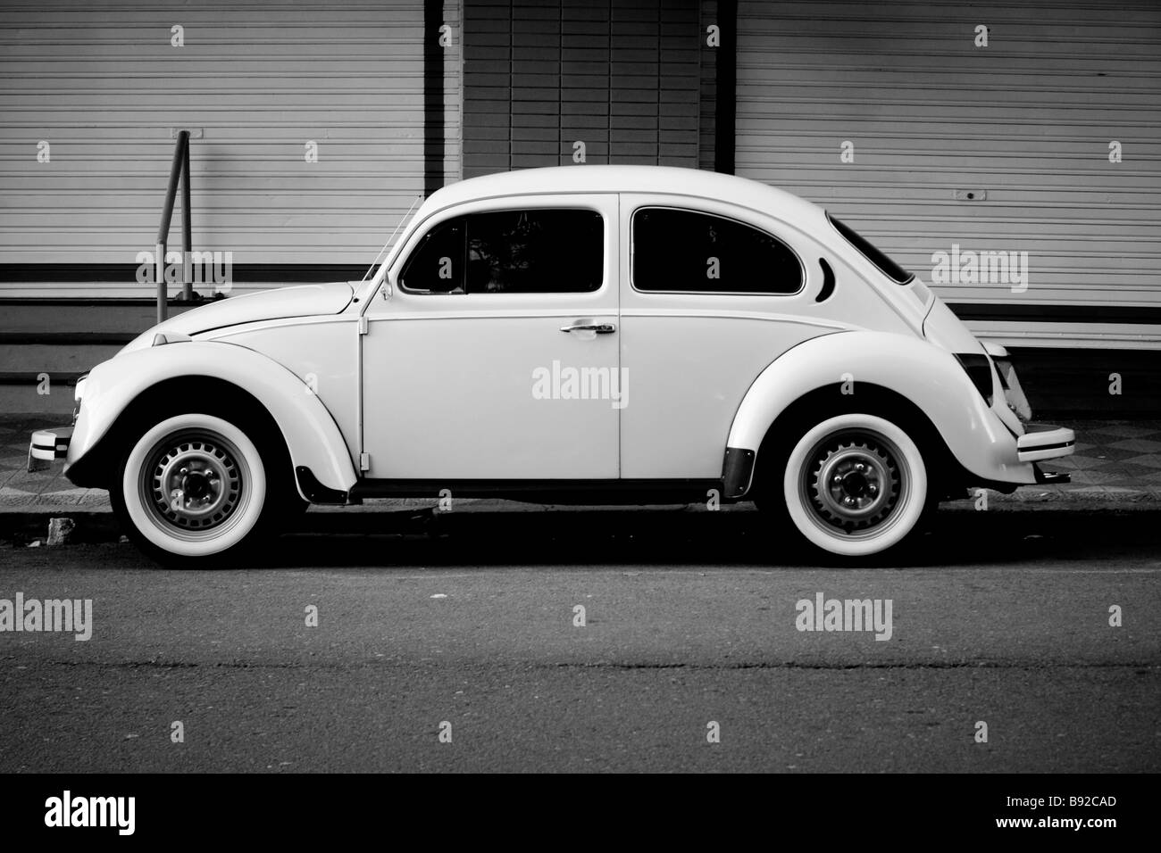 vintage white volkwagen beetle with white side tires parked on the street - Stock Image