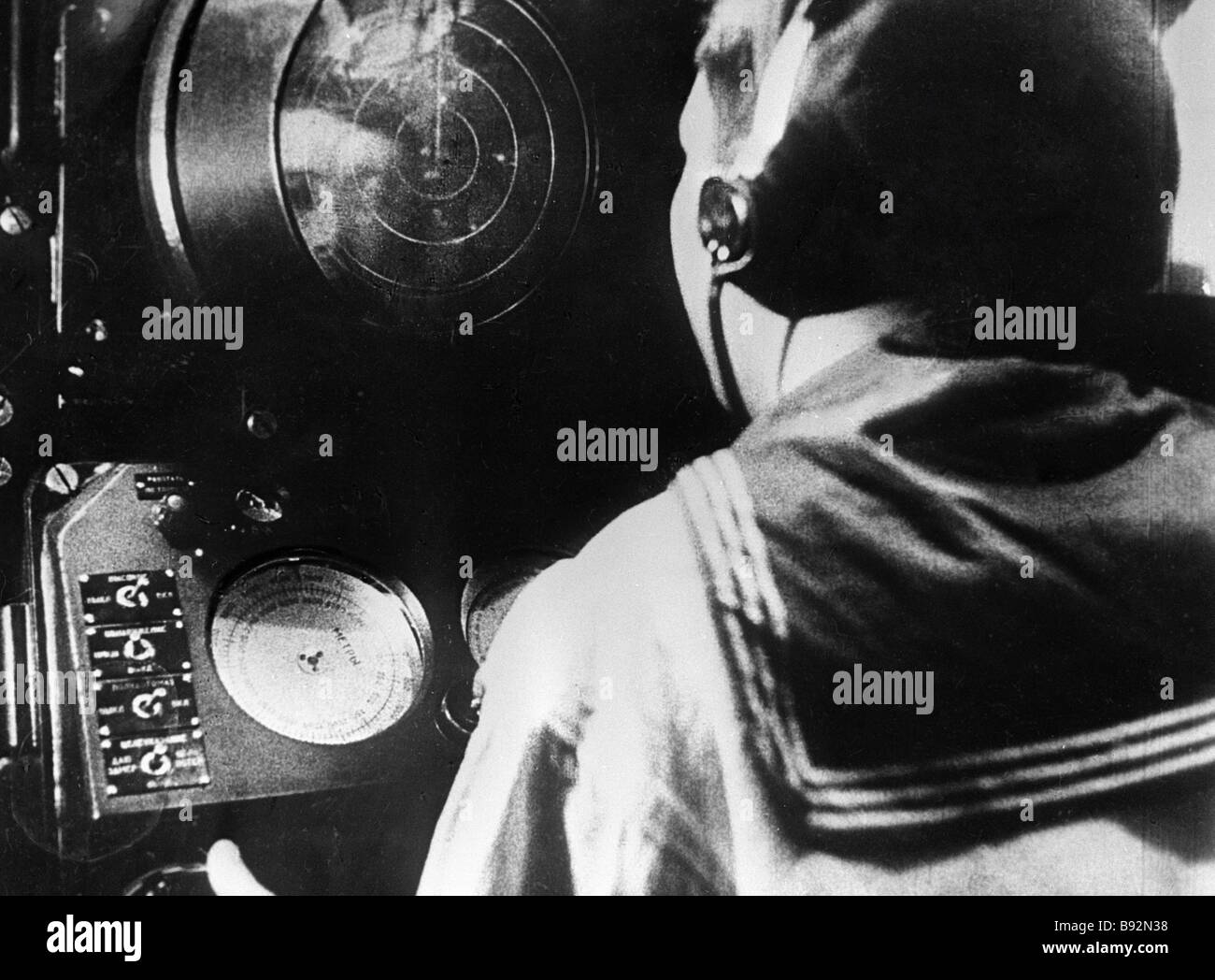 Sailor watches approaching objects on radar - Stock Image
