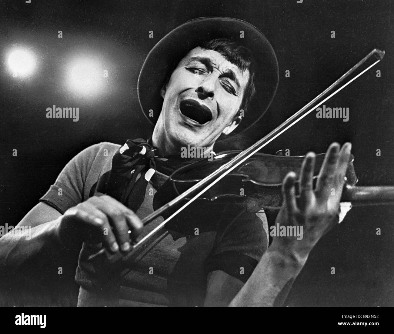 Clown and mime Leonid Yengibarov performing a gag with a fiddle - Stock Image