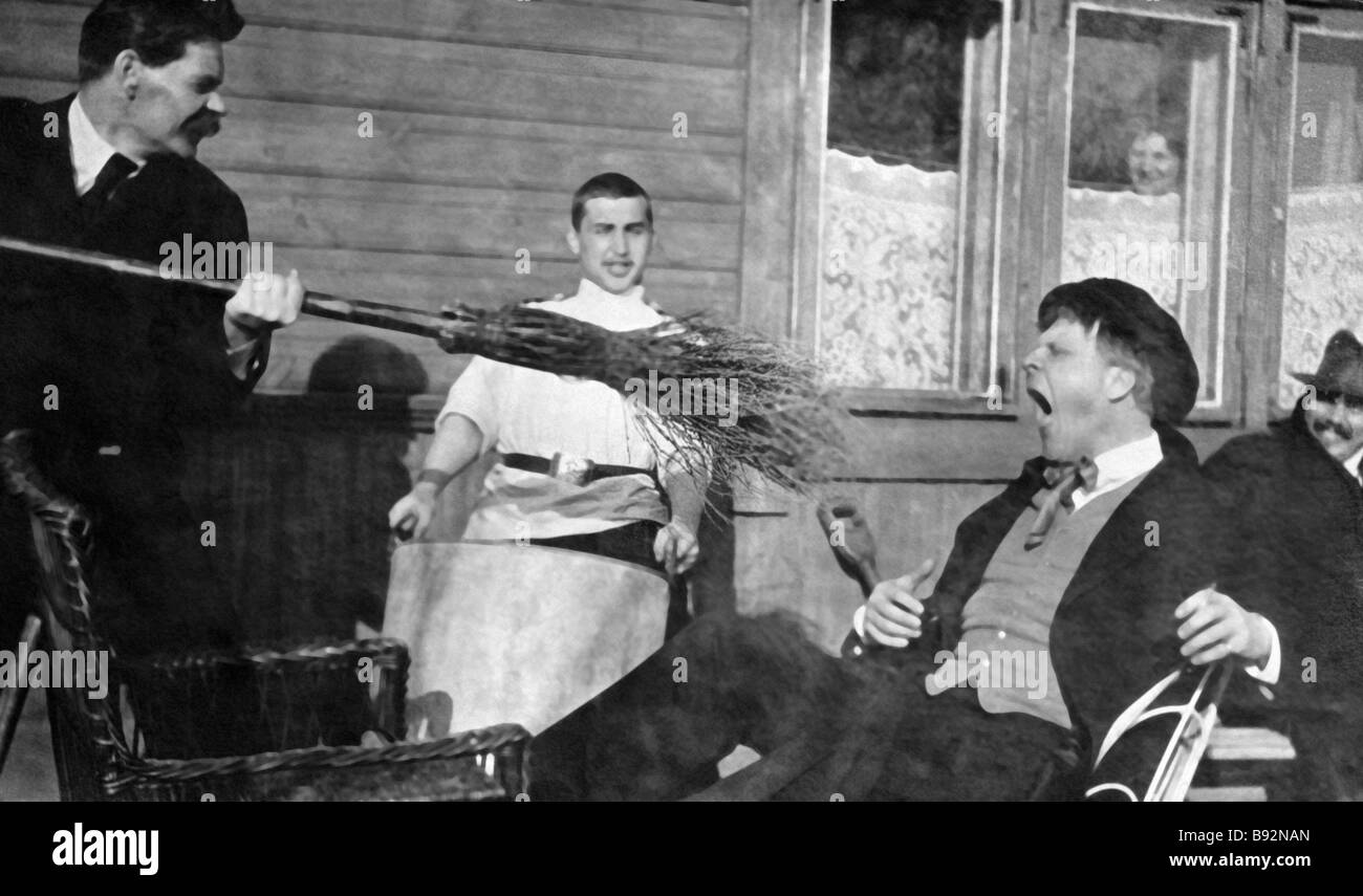 A comic photo writer Maxim Gorky left threatening singer Feodor Chaliapin right with a broom - Stock Image