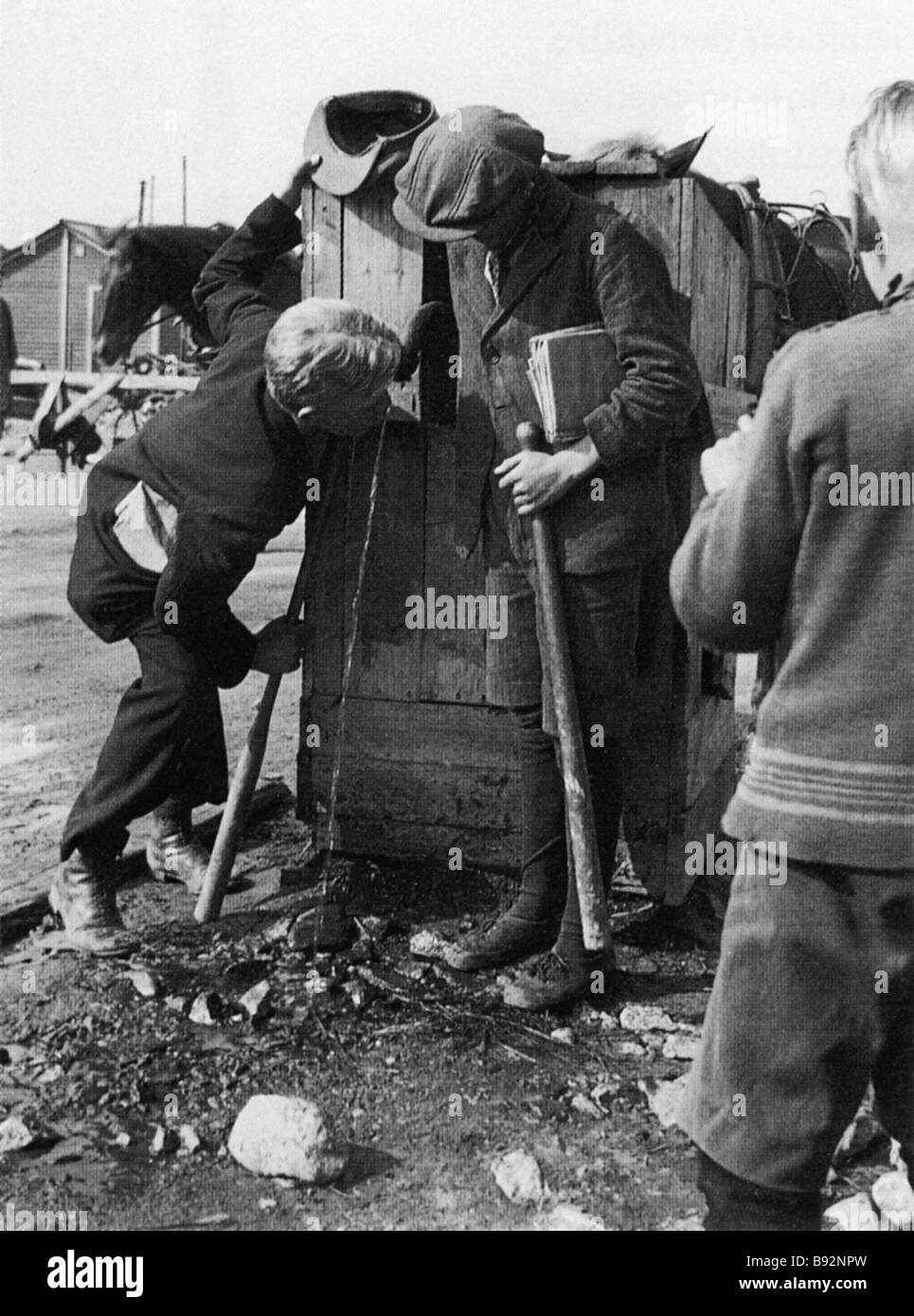 Boys drinking from Helsinki s first street water fountain The photograph is exhibited in the city Water Museum - Stock Image