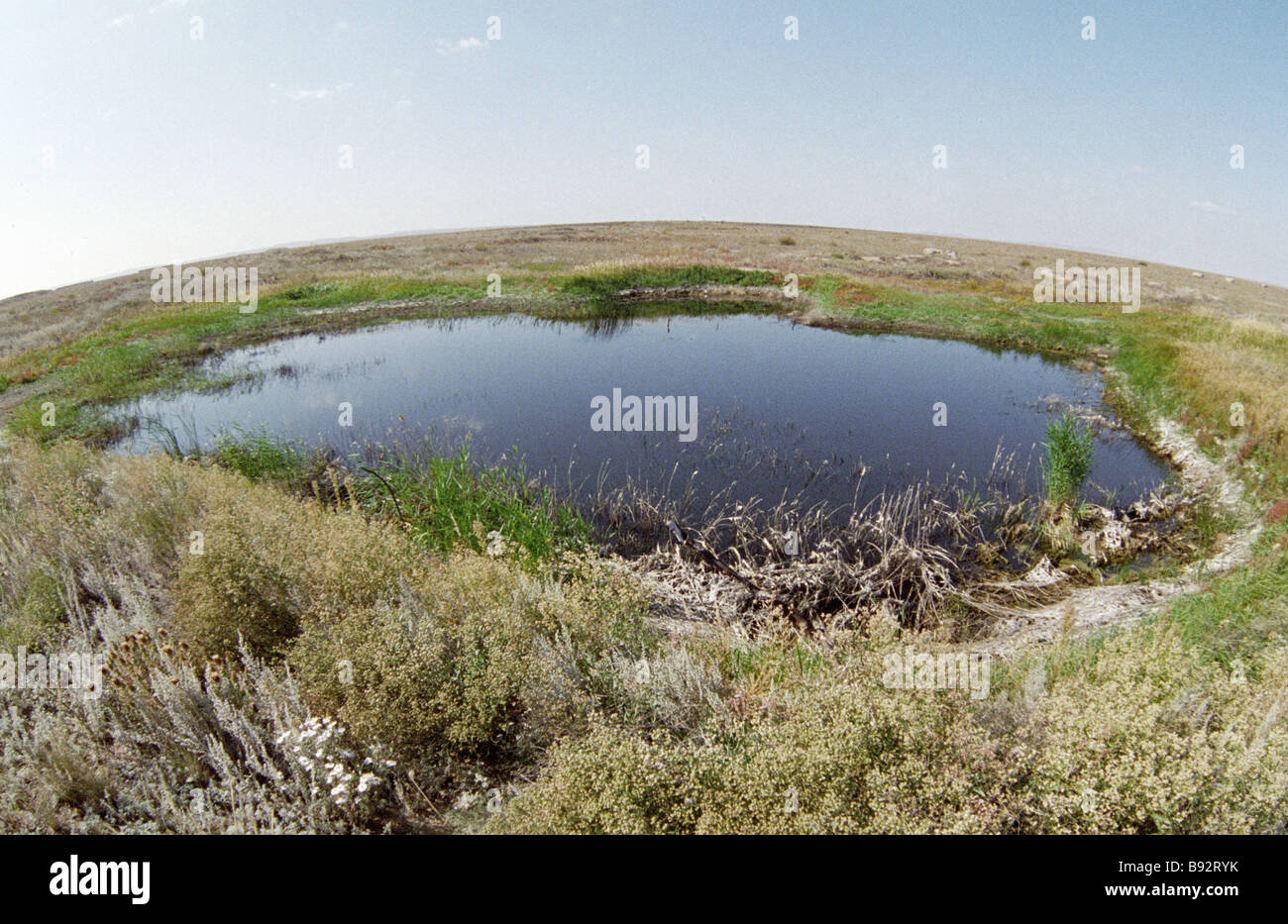 A lake in the place of a surface nuclear explosion on the Semipalatinsk proving ground - Stock Image