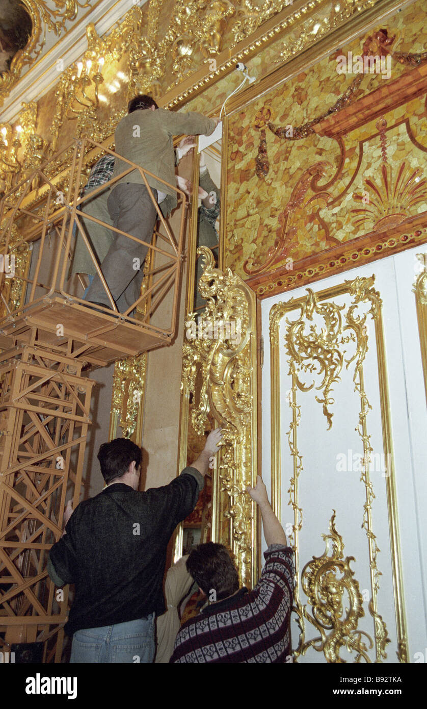 Restorers installing panels in Amber Room - Stock Image