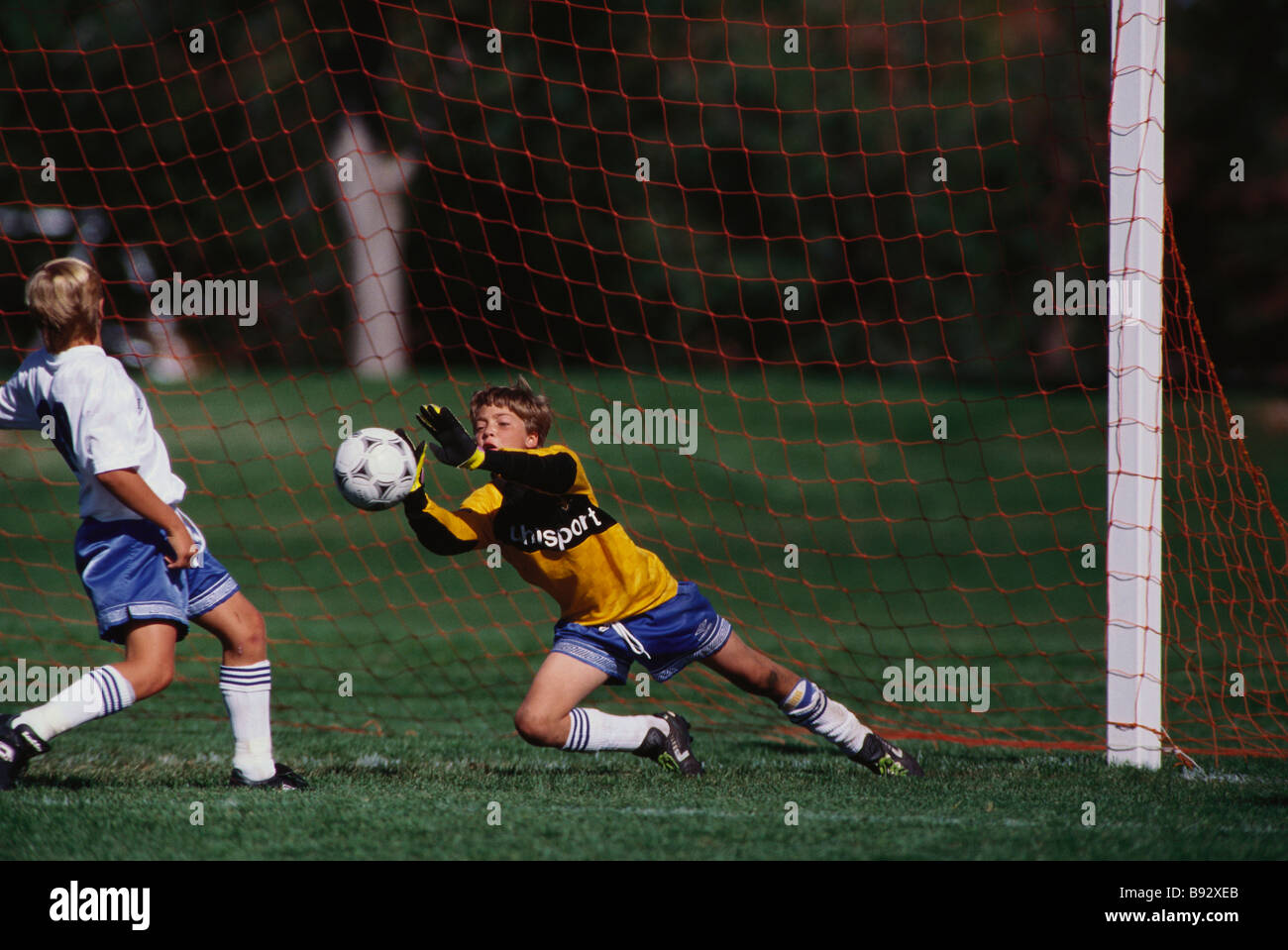 11 year old boys soccer goalie in action Stock Photo