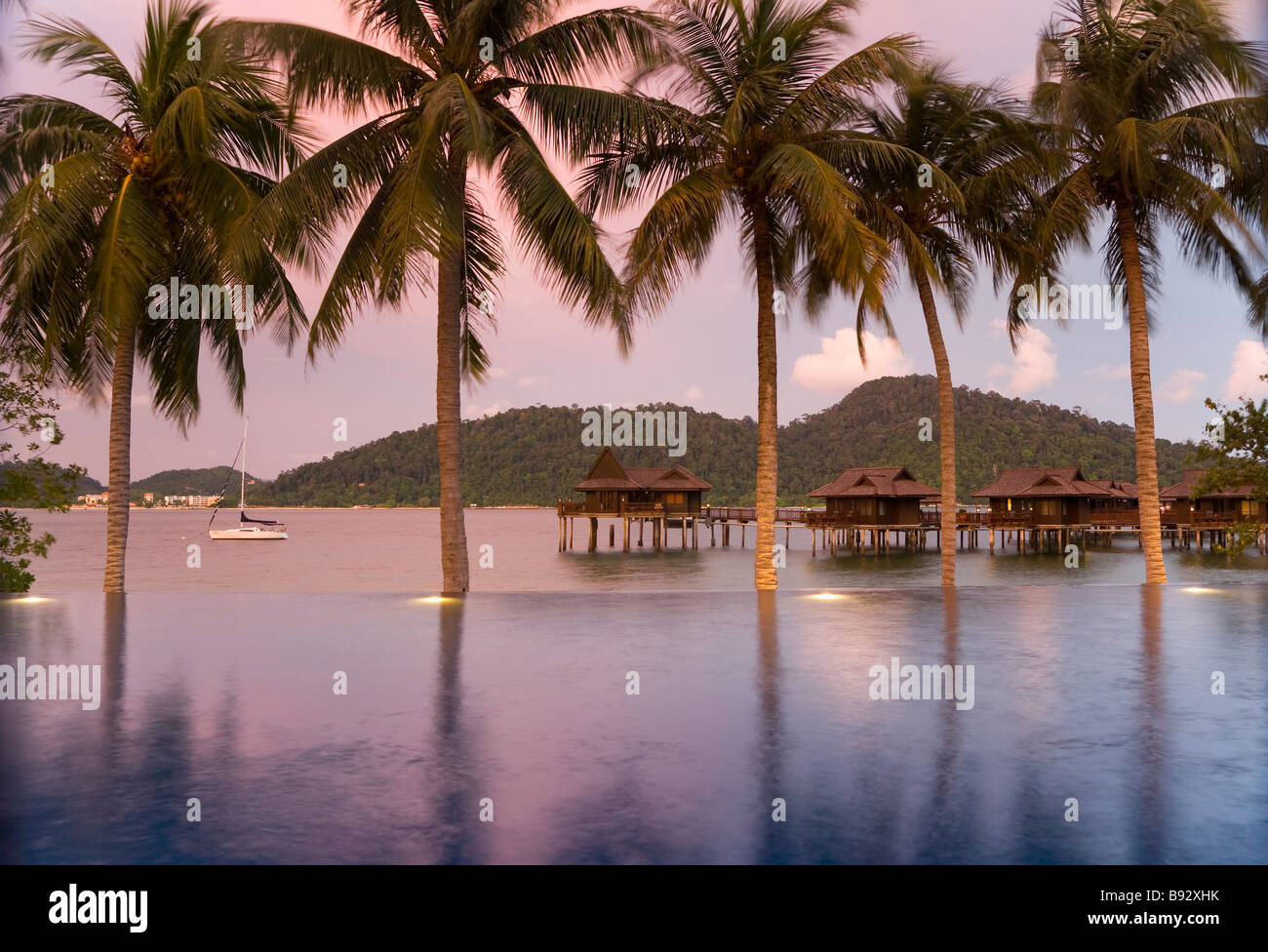 Sea houses through palm trees - Stock Image