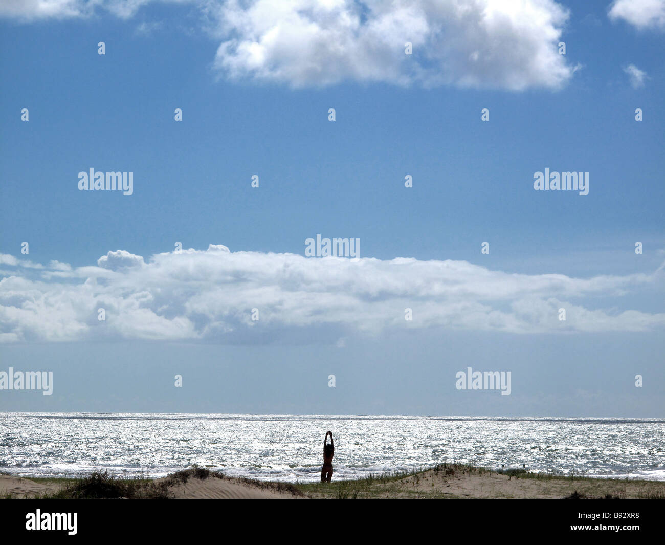 A woman performing yoga exercises by the beach in the morning - Stock Image