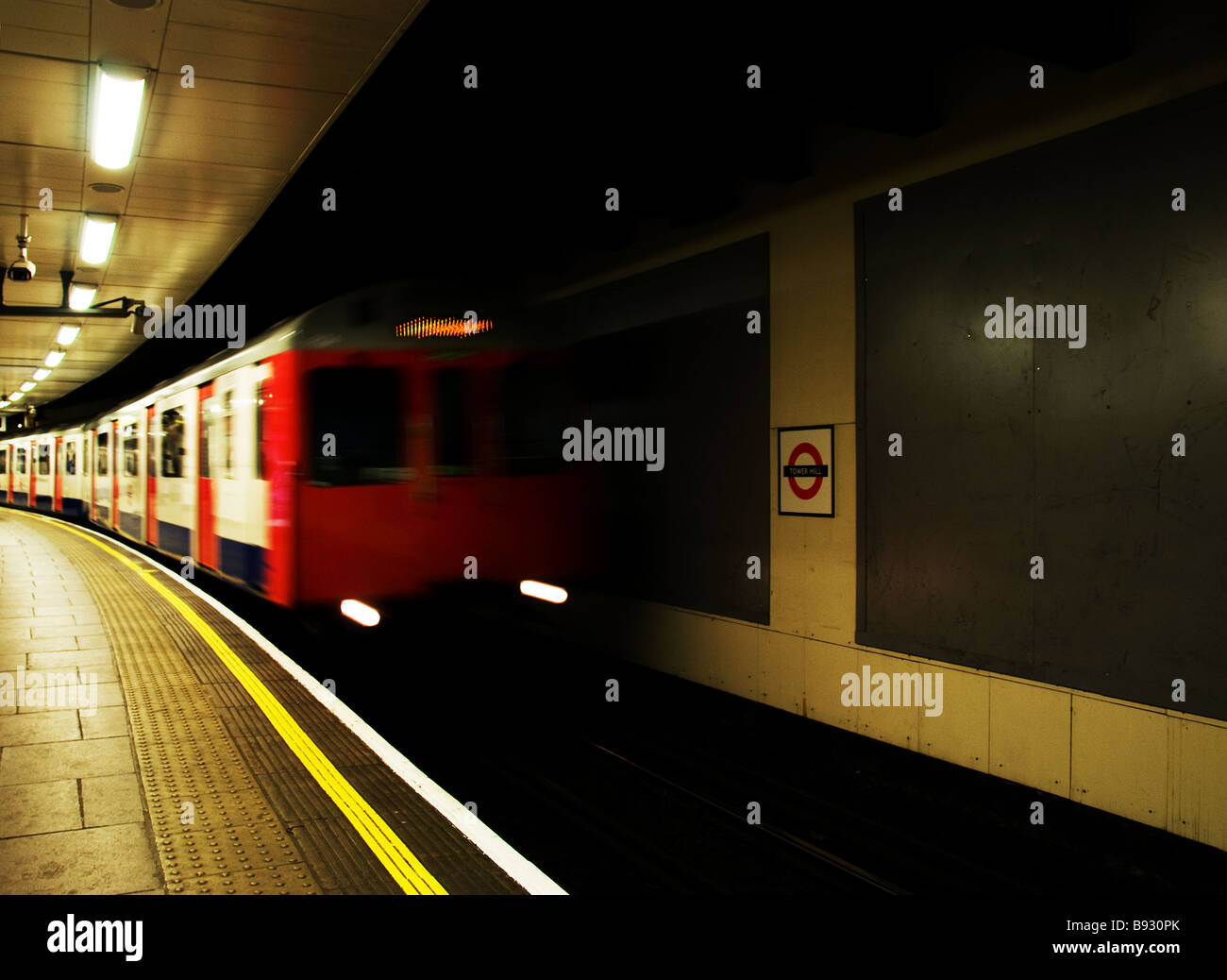 A London Tube train speeding into a station. - Stock Image