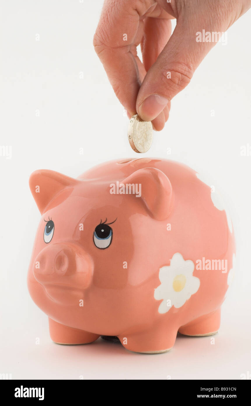 Pound coin being put into a piggy bank - Stock Image