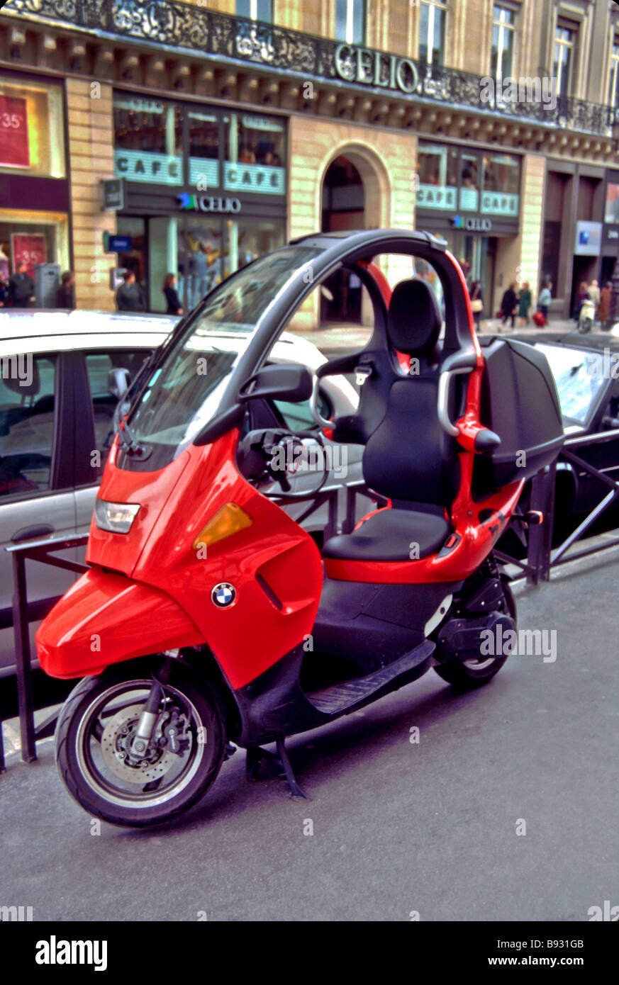 A BMW C1 enclosed scooter is parked on a Paris sidewalk - Stock Image