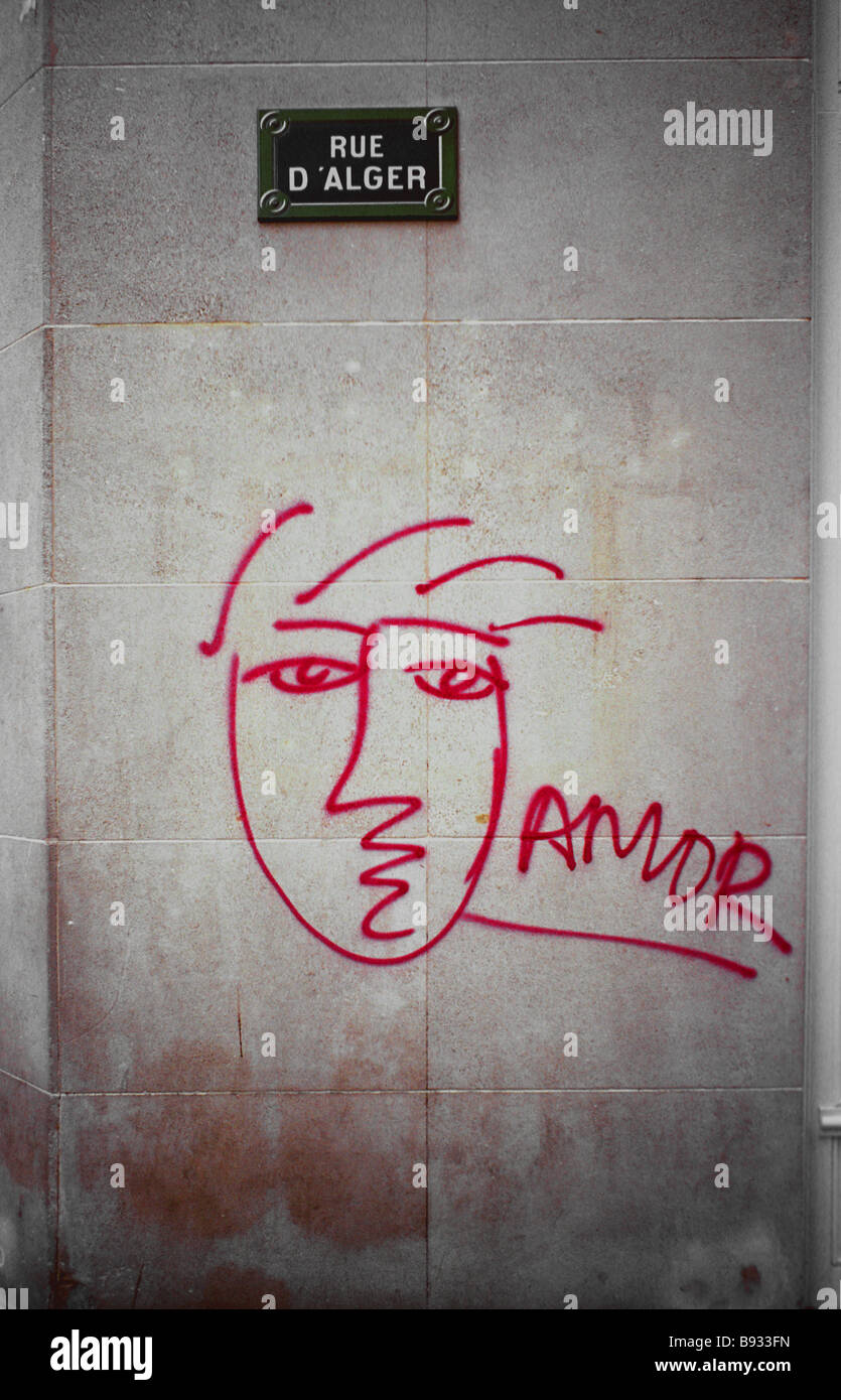 A purple spray painted cubist style image of a woman along with the word amour decorates a Paris street corner - Stock Image