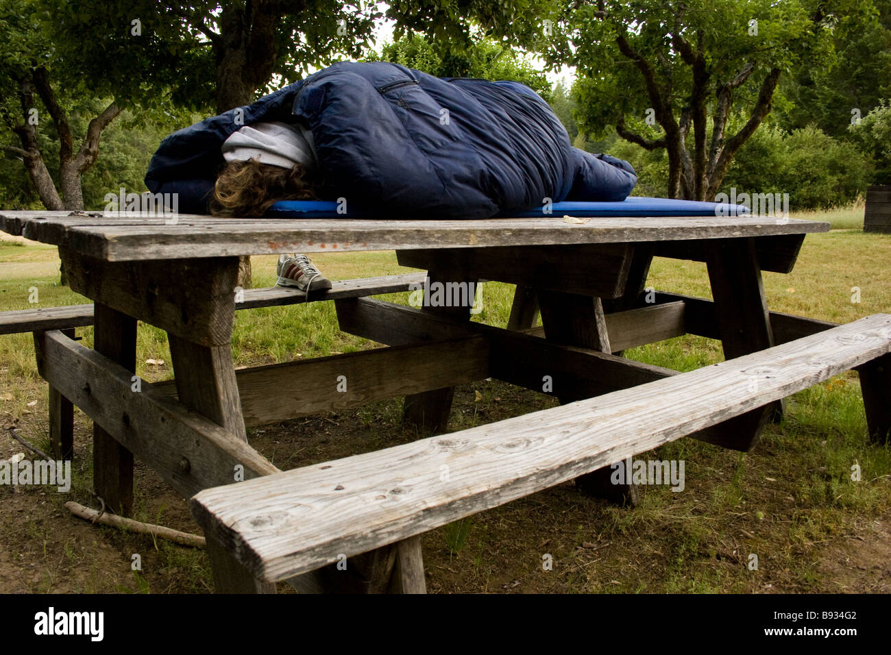 Person Sleeping In A Sleeping Bag On A Picnic Table.