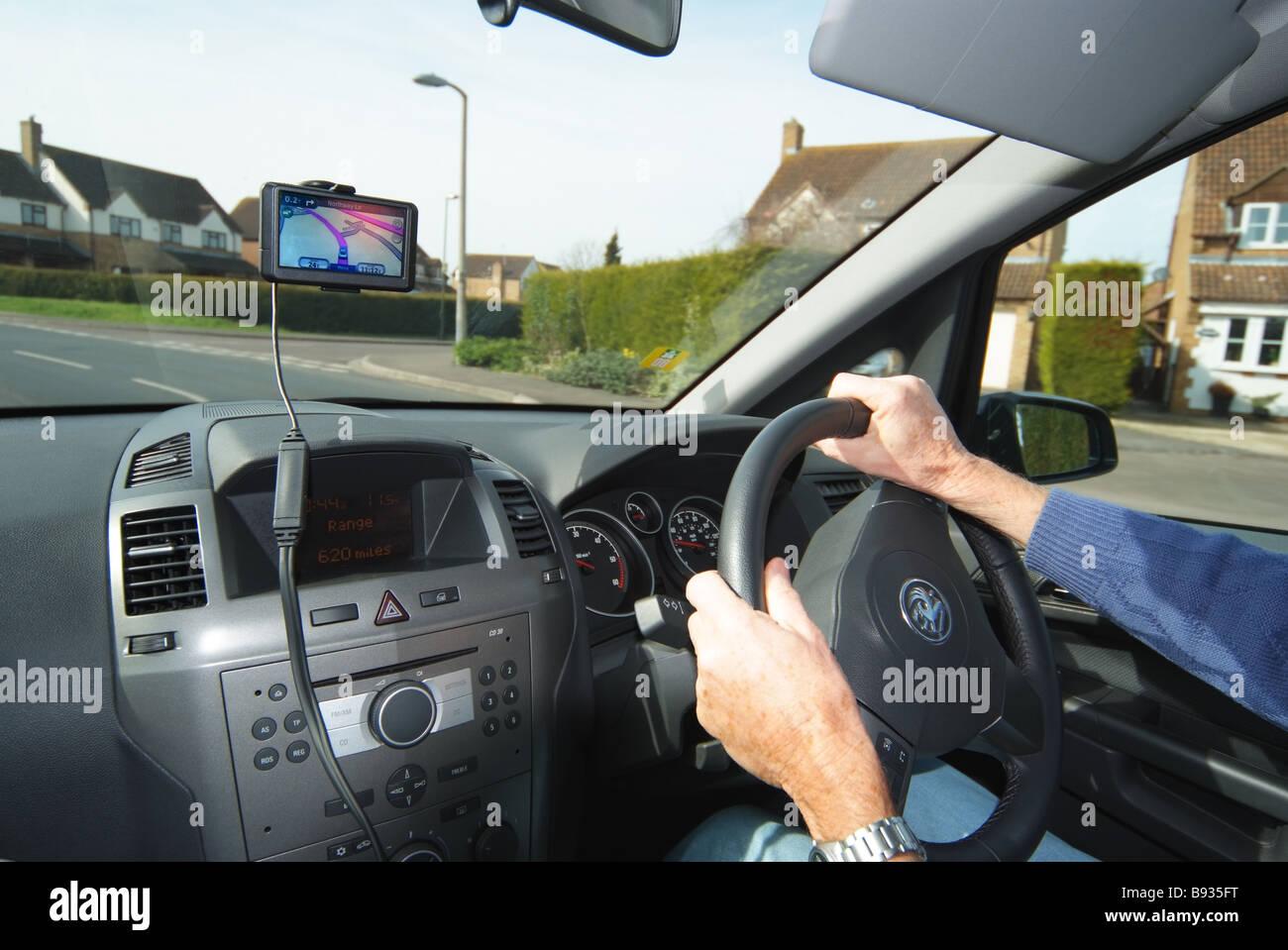 CAR DRIVER USING SATELLITE NAVIGATION EQUIPMENT - Stock Image
