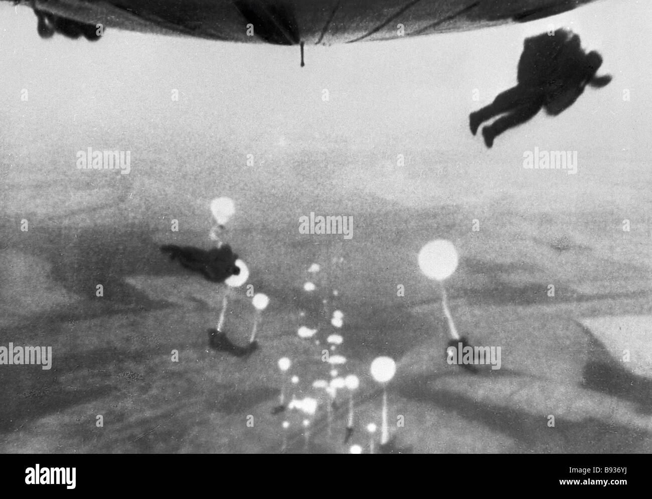 Paratroopers jump from military transport aircraft - Stock Image