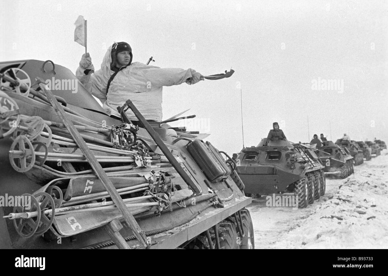 Column of armored cars with attached skis on the winter road - Stock Image