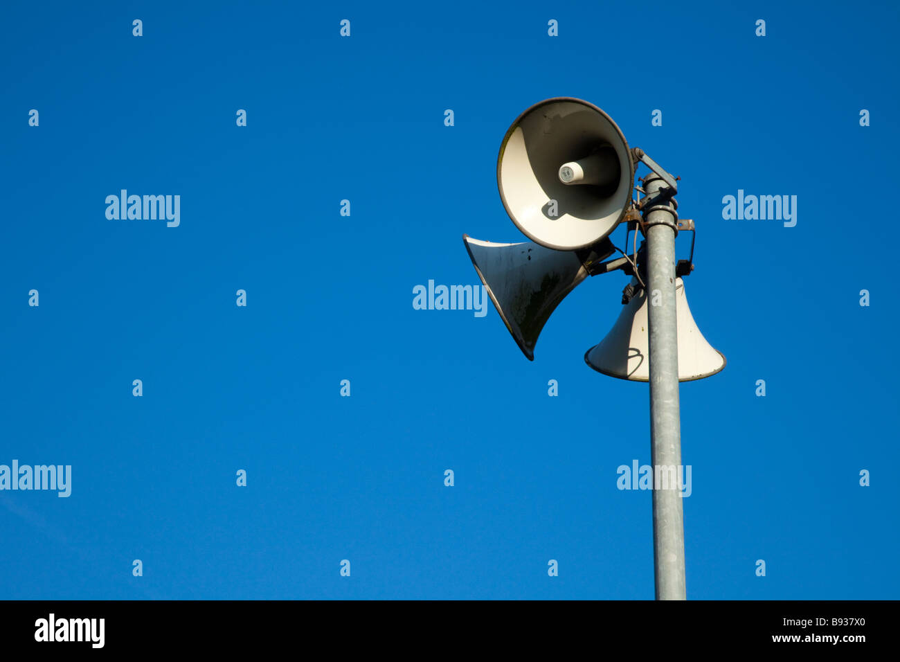 Loud tannoy speakers on a pole against a clear blue cloudless sky at Chester Race Course, Cheshire, England,UK - Stock Image