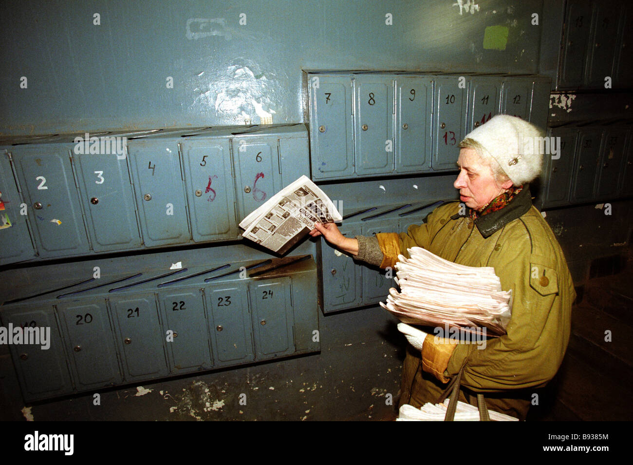 Post woman placing fresh newspapers inside mailboxes at apartment house entrance - Stock Image