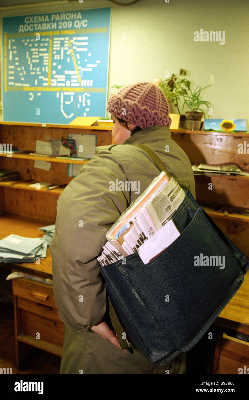 Post woman with heavy bag on shoulder ready to deliver mail - Stock Image